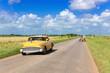 Amerikanischer gelber Oldtimer unterwegs auf der Landstrasse nach Havanna in Cuba - Serie Kuba Reportage