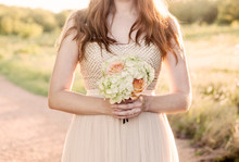 Midsection Of Woman Holding Bouquet Of Flowers Outdoors