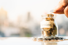 Concepts Of Retirement Planning And Financial. Man's Hand Holding Coin To Put In Glass Money Jar With Pension Label.
