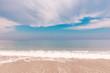 Idyllic seascape with surf line and beautiful clouds over sea. The sea foam at coastal line. Summer paradise beach.