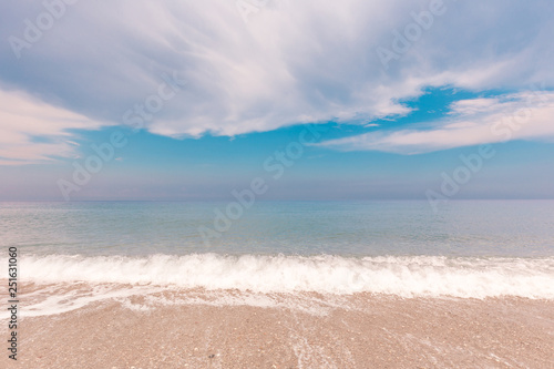 Idyllic seascape with surf line and beautiful clouds over