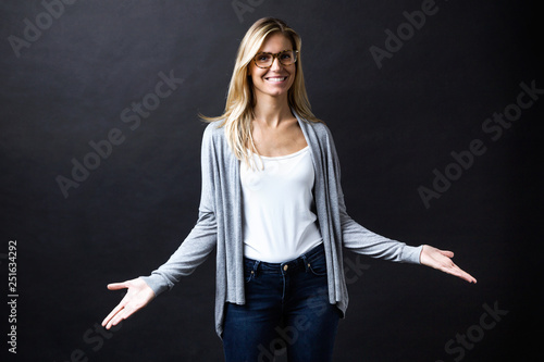 Fotografía  Smiling beautiful young woman with eyeglasses in doubt doing shrug showing open palms looking at the camera over black backgound