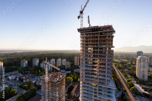 Obraz Aerial view of a residential building construction site during a vibrant summer sunset. Taken in Burnaby, Vancouver, BC, Canada. - fototapety do salonu
