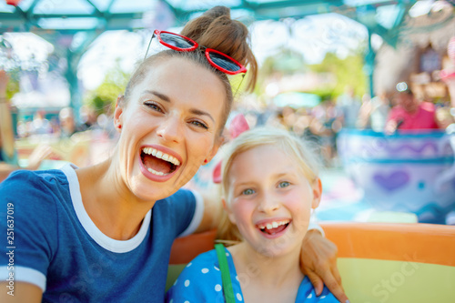 In de dag Amusementspark mother and child tourists in theme park enjoying attraction