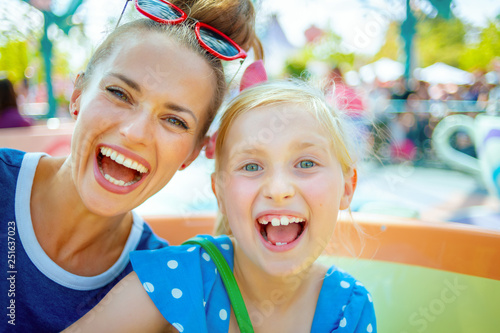 Foto  smiling mother and child tourists in theme park having ride
