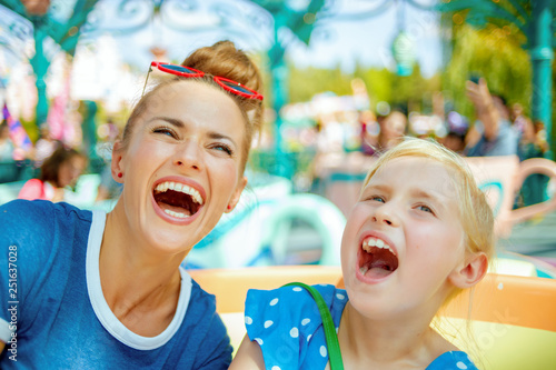 Poster Attraction parc mother and child travellers in amusement park enjoying ride