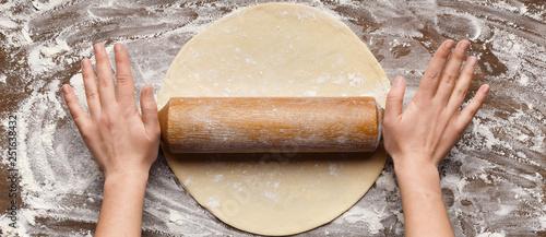 Chef rolling dough for pizza on table Slika na platnu
