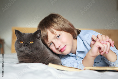 Fotografía  Adorable kid boy and british shorthair  cat lying together on the bed at home