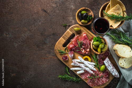 Fotografia  Antipasto - sliced meat, ham, salami, olives and wine  top view.
