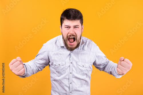Fotografering  aggressive man screaming clenched fists on orange background