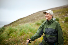 Woman Smiles As She Stops To Admire The Scenery On A Hike.