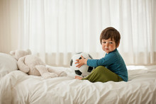 Young Boy Playing On A Bed Ins...