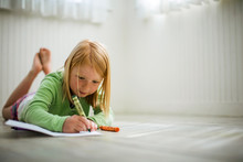 Happy Young Girl Coloring With...