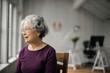 Senior woman with gray hair looking through window