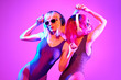 canvas print picture - Two shapely fashionable DJ girl dance enjoy music in colorful neon uv purple blue light. Rave house music night club vibes. High Fashion. Young model woman friends relax, neon makeup.