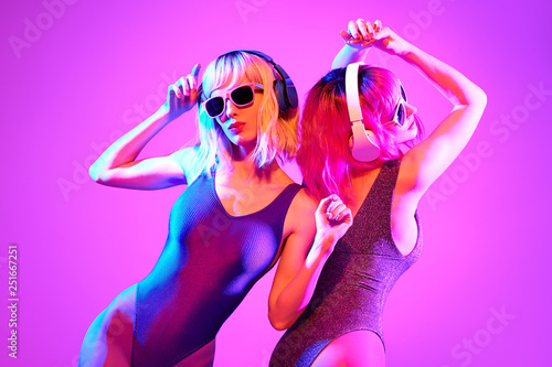 Two shapely fashionable DJ girl dance enjoy music in