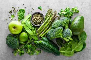 FototapetaHealthy vegetarian food concept background, fresh green food selection for detox diet, raw broccoli, apple, cucumber, spinach, peas, asparagus, avocado, lime, corn salad and mung bean, view from above