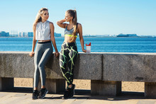Two Happy Fit Sports Girls Have A Rest On The Embankment Or In The Park Against The Background Of The Sea After Training Or Workout. Healthy Lifestyle Concept