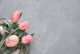 Fototapeta Tulipany - Springtime or Easter background with pink tulips and Easter eggs in wattle ring on grey concrete, text space