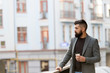 Beginning of busy day. Hipster with paper cup walking in city. Businessman in hipster style holding takeaway coffee. Bearded man enjoying morning coffee. Drinking his cup first thing in the morning