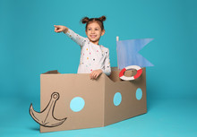 Cute Little Girl Playing With Cardboard Boat On Color Background
