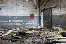 Various Wood Debris Blocking Passage Way In An Abandoned Factory With Chipping Paint
