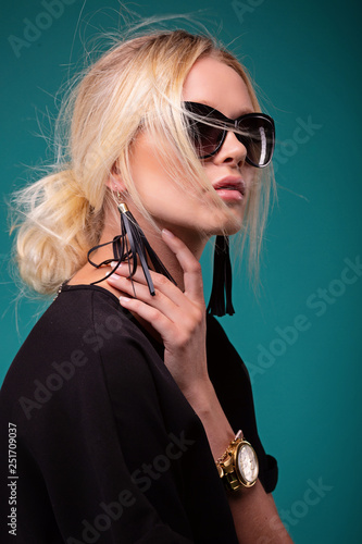 Valokuva  Beautiful glamorous woman in dark round glasses and in a black dress on a blue b
