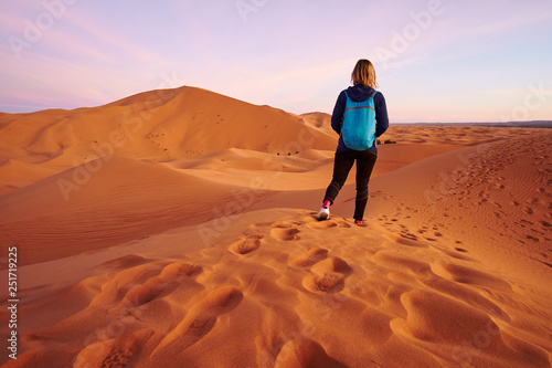 Keuken foto achterwand Marokko Tourist blonde girl walking on the sand dune in Sahara desert Morocco Africa