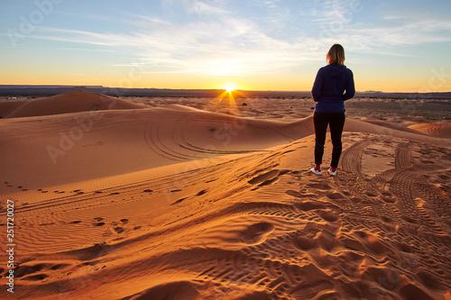 Keuken foto achterwand Marokko Blonde tourist girl watching sunrise in Sahara desert on top of the sand dune in Merzouga Morocco Africa