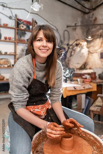 Fotografia, Obraz Happy woman working on potter wheel in pottery workshop