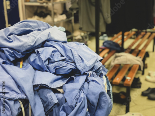 Fotografie, Obraz  A clothes basket overflowing with surgical scrubs in the changing room of a hospital in the United Kingdom - untidy environment of the locker room