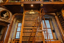 Vienna, Austria - December 24, 2017. Interior Of Austrian National Library With Wooden Ladder And Bookshelves. Hapsburg Empire's Old Baroque Library Hall With Rare Ancient Folios And Old Maps.