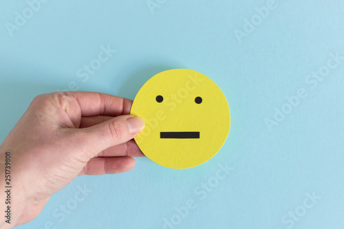 Crop hand with yellow indifferent smiley Slika na platnu