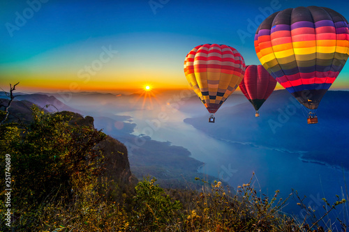 Poster Montgolfière / Dirigeable Colorful hot air balloons flying in sunrise over mountain and Ping River at Pha Daeng Luang, Mae Ping National Park, Lamphun in Thailand