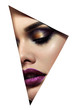 canvas print picture The face of a young beautiful girl with bright makeup and full purple lips peers into a triangular hole in white paper.