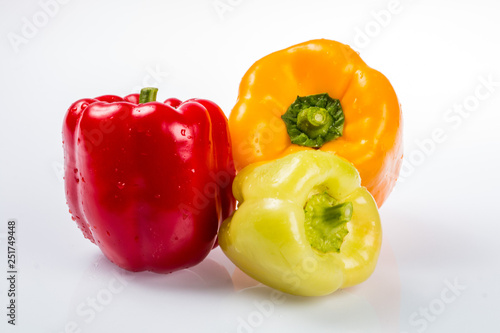 Fotografia Three delicious ripe Bulgarian peppers, lime, red, orange, with green tails in t