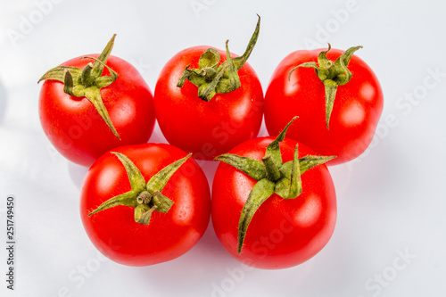 Five delicious ripe tomatoes with green tails in the same plane on a white backg Fototapet