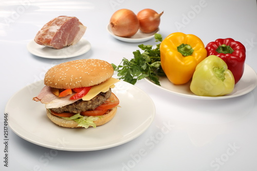 cheeseburger with bacon and beef patty on a plate with vegetables, bell pepper, Fotobehang