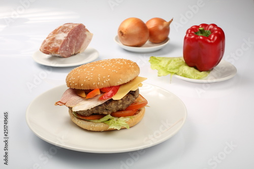 Valokuva  cheeseburger with bacon and beef patty on a plate with vegetables, bell pepper,