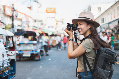 Asian woman tourist backpacker travel and taking photo in Khao San road, Bangkok, Thailand