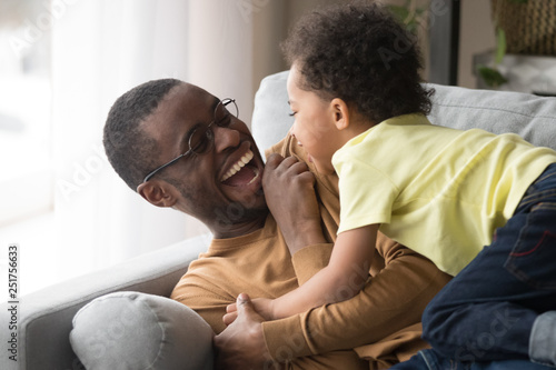 Obraz Happy african dad laughing playing with little toddler son together - fototapety do salonu