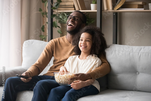 Fotografie, Tablou  Cheerful african american father and child girl laughing watching tv