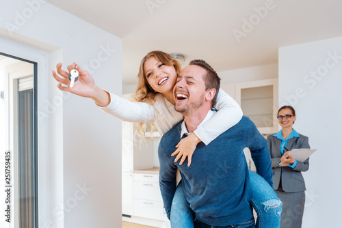 Fotografie, Obraz  Man carrying his wife piggyback who is showing the house keys
