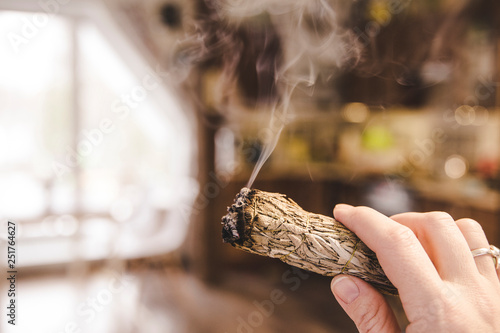 Fotografiet  Woman hand holding herb bundle of dried sage smudge stick smoking