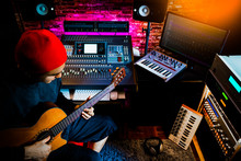 Asian Male Musician Recording Acoustic Guitar Track In Home Studio