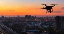 Silhouette Of Drone Flying Above City At Sunset