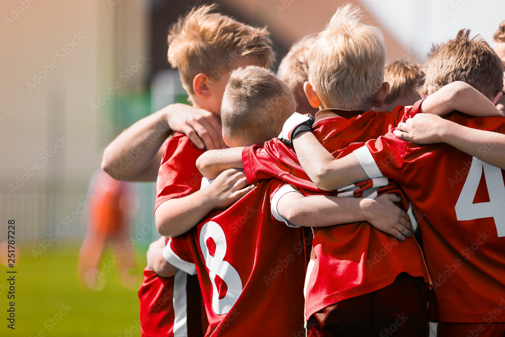 Fototapety, obrazy: Kids Play Sports Game. Children Sporty Team United Ready to Play Game. Children Team Sport. Youth Sports For Children. Boys in Sports Jersey Red Shirts. Young Boys in Soccer Sportswear