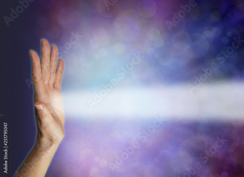 Energy being received by Pranic healer's left hand palm chakra - female hand facing out with a beam of white energy streaming out against a blue bokeh energy field background with copy space