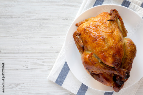 Fotografia Homemade tasty rotisserie chicken on white plate, top view