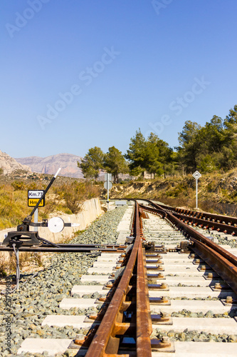 Fotografía  A railroad switch track with traffic signs, mountains and trees in the backgroun